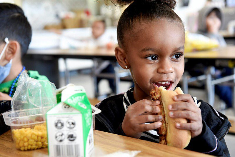 A young female Fresno Unified student eats pizza in the cafeteria